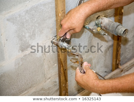 plumber fixing copper pipe to wall stock photo © photography33