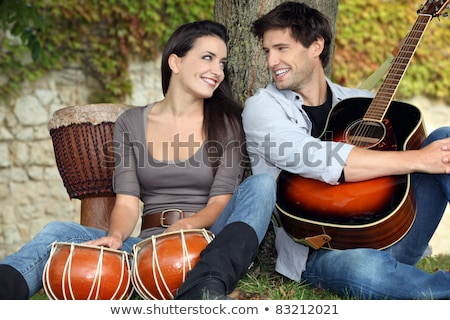 Stock photo: Couple playing drums and a guitar under a tree