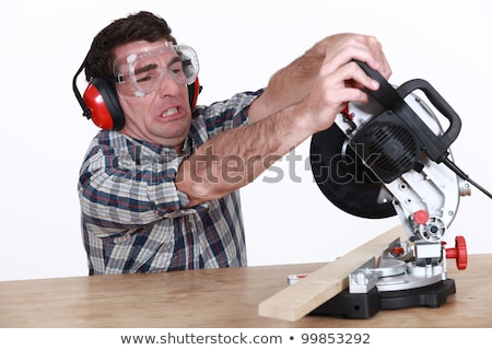 Man struggling to use a mitre saw Stock photo © photography33