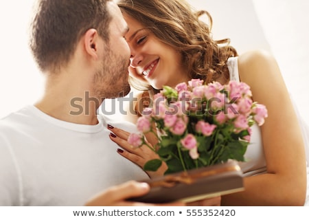 kissing in bed with flowers stock photo © dolgachov