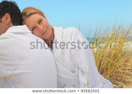 Couple sitting in the sand dunes in white toweling robes Stock photo © photography33