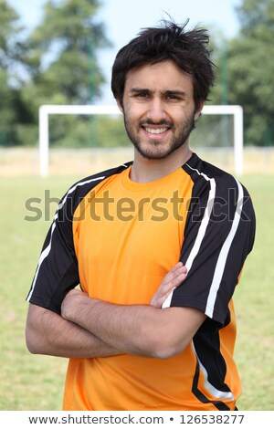 Footballer with arms crossed standing on pitch with goal in the background Stock photo © photography33