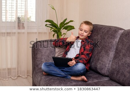 young child on couch with earmuffs Stock photo © gewoldi