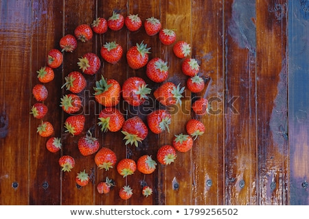 Strawberry and cherry on the old brown wooden background. Stock photo © justinb