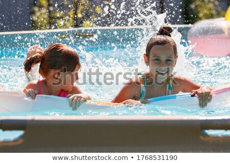 two girls lying on air mattress in swimming pool stock photo © deandrobot