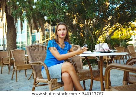 Young pretty modern blogger using smartphone and makes notes in  Stock photo © vlad_star