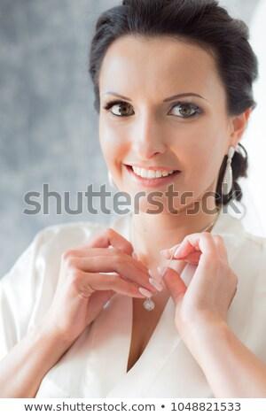 Pretty woman in robe adjusting hair Stock photo © dash