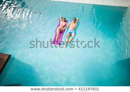 Lovely young woman floating in a swimming pool Stock photo © dash