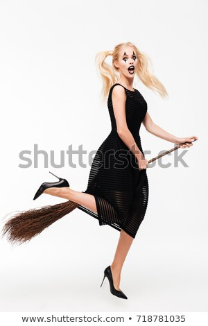 Beautiful young woman in black witch halloween costume with broom Stock photo © deandrobot
