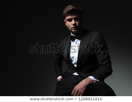 happy elegant man in tuxedo and bowtie is sitting Stock photo © feedough