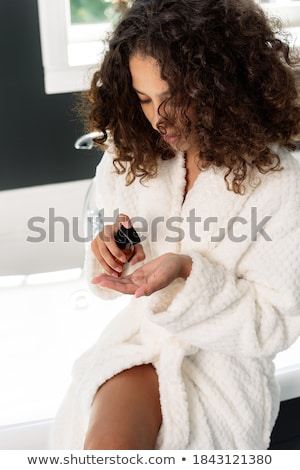 A young woman sitting in the bathroom using body lotion Stock photo © monkey_business