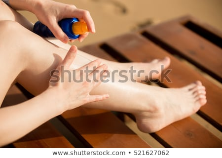 Slim tanned woman applying cosmetics Stock photo © hannamonika