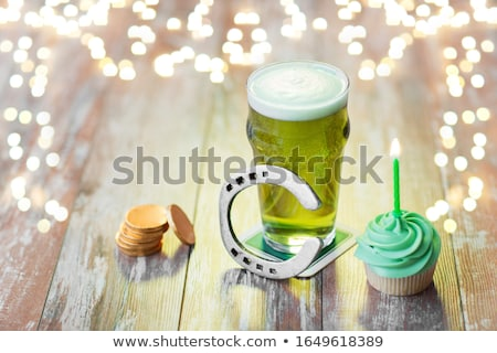glass of beer, cupcake, horseshoe and gold coins Stock photo © dolgachov