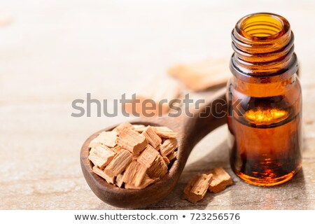 a bottle of sandalwood essential oil with sandalwood on a wooden spoon stock photo © madeleine_steinbach