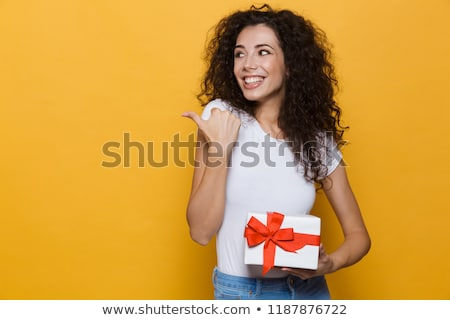 Cute young woman posing isolated over yellow background holding gift box present. Stock photo © deandrobot