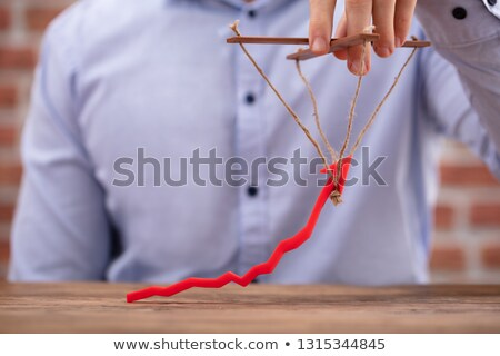 Person's Hand Manipulating Blue Arrow With Rope Stock photo © AndreyPopov