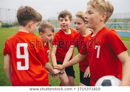 Happy kids soccer team huddling and stacking hands together Stock photo © matimix