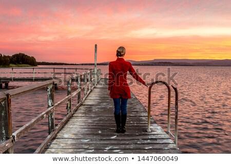 Woman on rustic timber jetty watching beautiful sunset Stock photo © lovleah