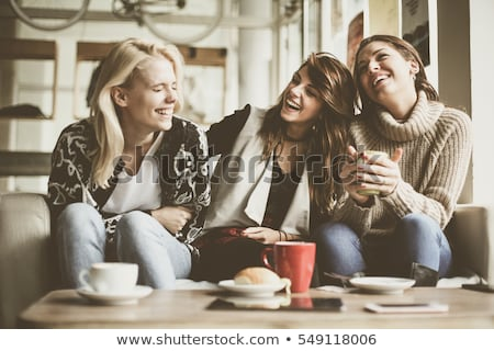 female friends drinking tea and talking at cafe Stock photo © dolgachov