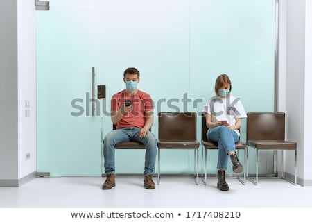 young woman sitting in hospital waiting for a doctors appointment patients in doctors waiting room stock photo © galitskaya