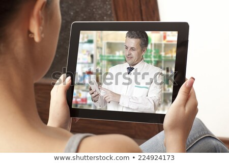 woman having video chat with pharmacist on laptop Stock photo © dolgachov