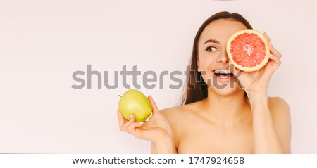 Pomelo fruit in beautiful female hands on a green background Stock photo © galitskaya