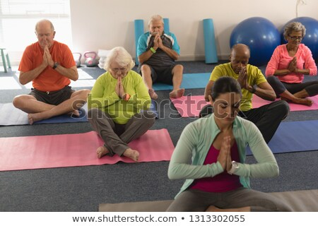 front view of concentrated senior people doing yoga with female trainer in fitness studio stock photo © wavebreak_media