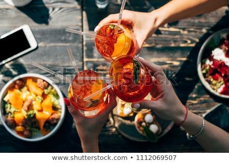 Group of friends cheers with aperol spritz in restaurant Stock photo © dashapetrenko
