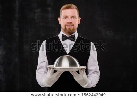 Happy elegant waiter in black waistcoat and bowtie and white shirt and gloves Stock photo © pressmaster