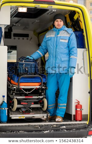 Young paramedic with first aid kit standing by stretcher inside ambulance car Stock photo © pressmaster