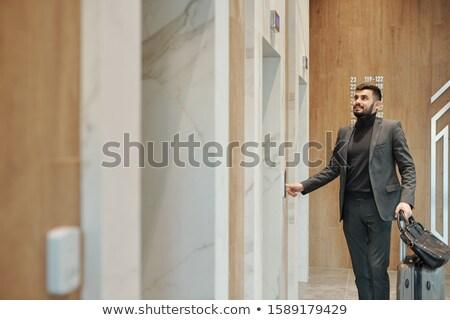 Contemporary business traveler in suit pushing elevator button on the wall Stock photo © pressmaster