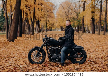 Outdoor shot of male biker with thick beard, wears protective gloves, black coat and jeans, poses on Stock photo © vkstudio