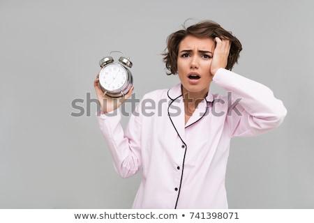 shocked young woman in pajama with alarm clock Stock photo © dolgachov