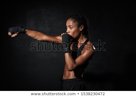 Image of young woman wearing sportswear training in boxing hand wraps Stock photo © deandrobot
