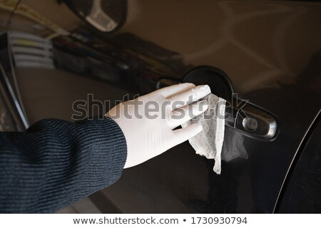 Driver cleaning car handle using sprayer Stock photo © simazoran