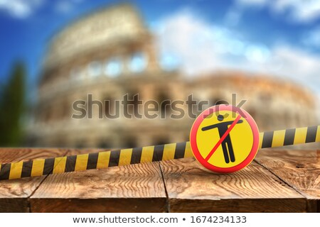 Warning sign with crossed out man on the background of wooden table and blurred Colosseum in Rome, I Stock photo © artjazz