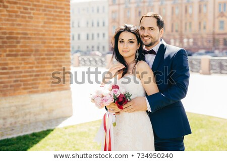 Married couple with happy expressions stand close to each other, embrace passionately, pose outdoors Stock photo © vkstudio