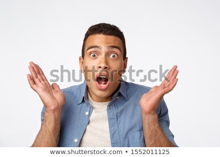 Close-up handsome masculine brazilian man in blue shirt over t-shirt, raising hands up stunned, open Stock photo © benzoix