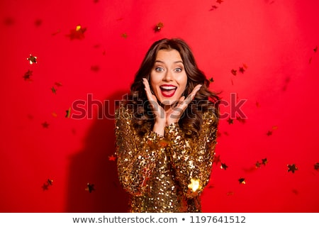 Shocked young woman in bright sequins dress Stock photo © deandrobot
