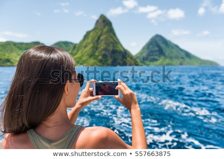 Cruise boat tourist taking mobile phone pictures of Deux pitons peaks, St-Lucia, Caribbean. The Gros Stock photo © Maridav