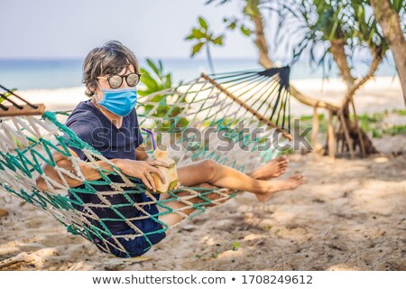 Young man in medical mask on the beach in a hammock with a drink Tourists fear the 2019-ncov virus.  Stock photo © galitskaya