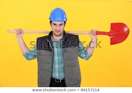 Scowling labourer carrying a shovel Stock photo © photography33