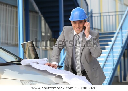 Stock photo: Architect looking at plans on a car bonnet