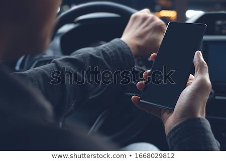 Car driver hands with cell phone. Stock photo © Kurhan