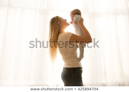 Young Caucasian woman lifting her baby son Stock photo © photobac
