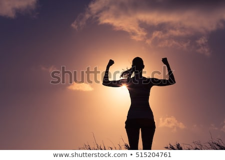 beautiful young woman standing and flexing biceps stock photo © bmonteny