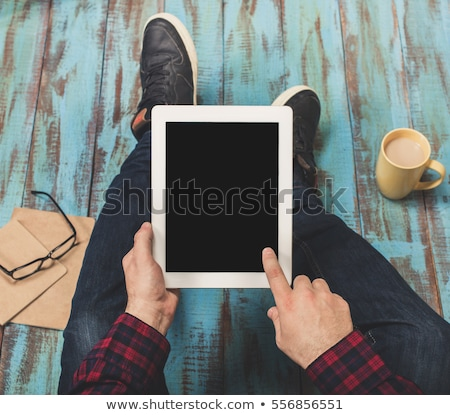 young man looking down while holding a tablet pad computer stock photo © feedough