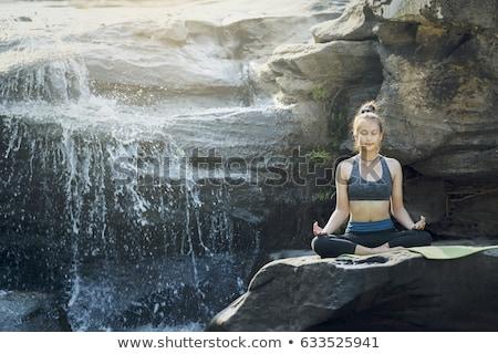Young woman meditating near the mountain river. Yoga practicing  Stock photo © Yatsenko