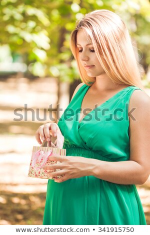 Happy pregnant woman pulls out a pink baby booties from a packag Stock photo © Yatsenko