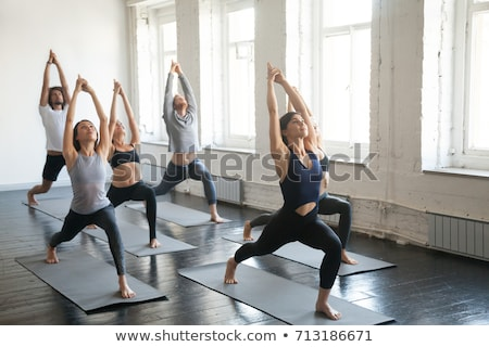 Male yoga trainer helping a woman to do yoga stretches Stock photo © deandrobot